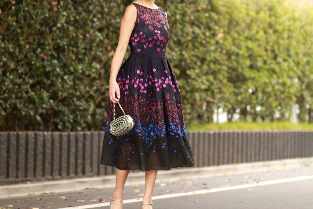 ネイビーのAラインドレスにパープル、ブルーで全体にお花の刺繍が施されている膝下丈の華やかなドレス