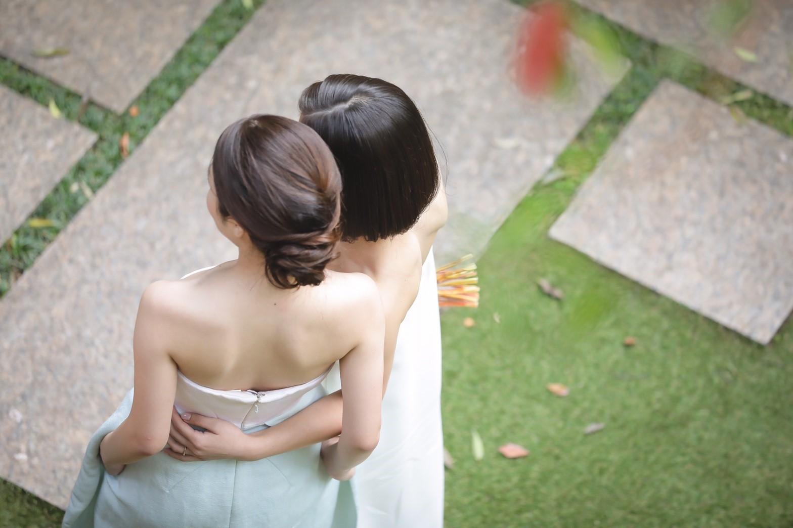 デルポソの白いベアトップで刺繍が施されたウェディングドレスを着ている花嫁とデルポソのベアトップで白とライトグリーンのバイカラーのドレスを着てる友人。女優Caitriona Balfeも同じドレスを着ていた。