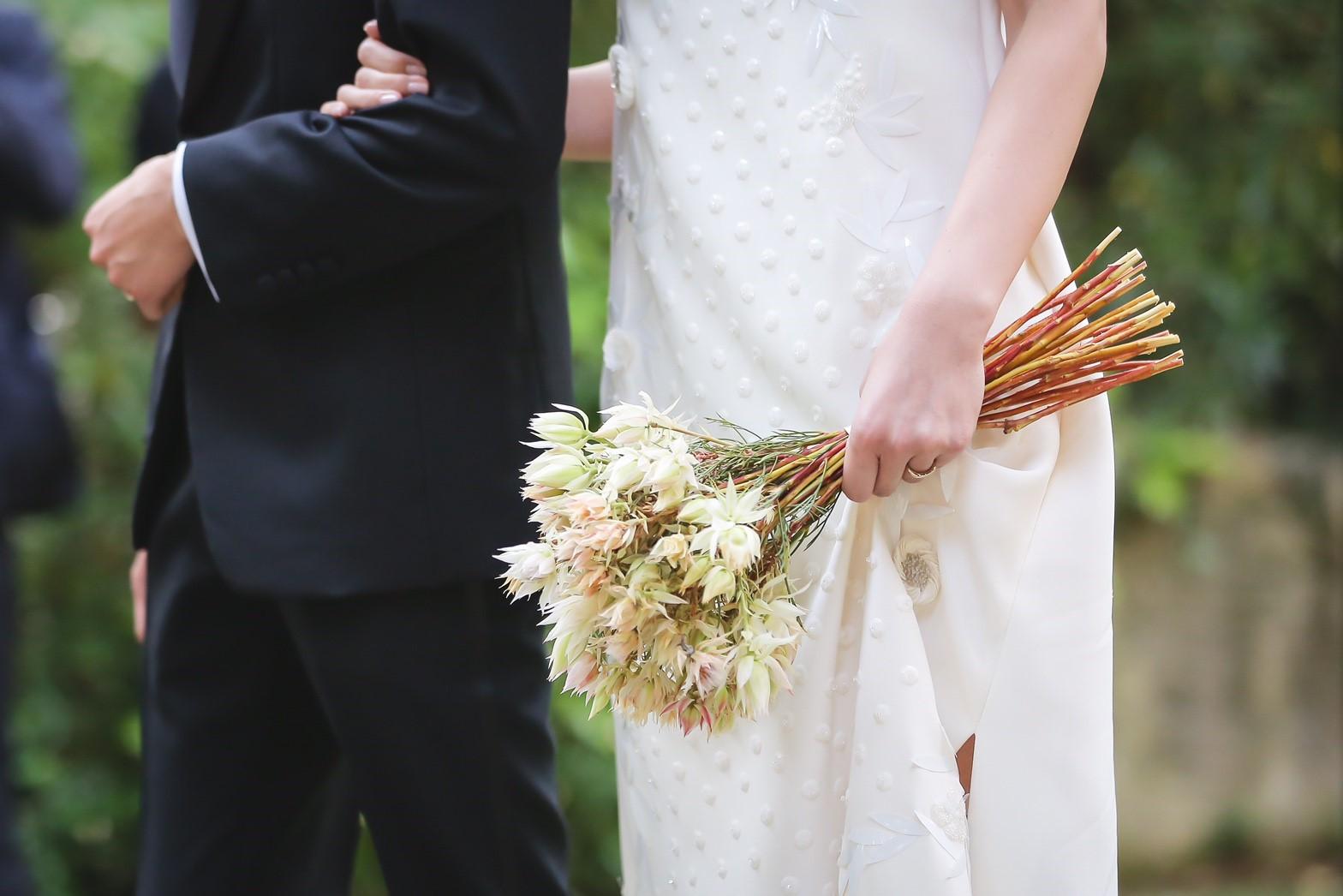 デルポソの白いベアトップで刺繍が施されたウェディングドレスを着ている花嫁と新郎。