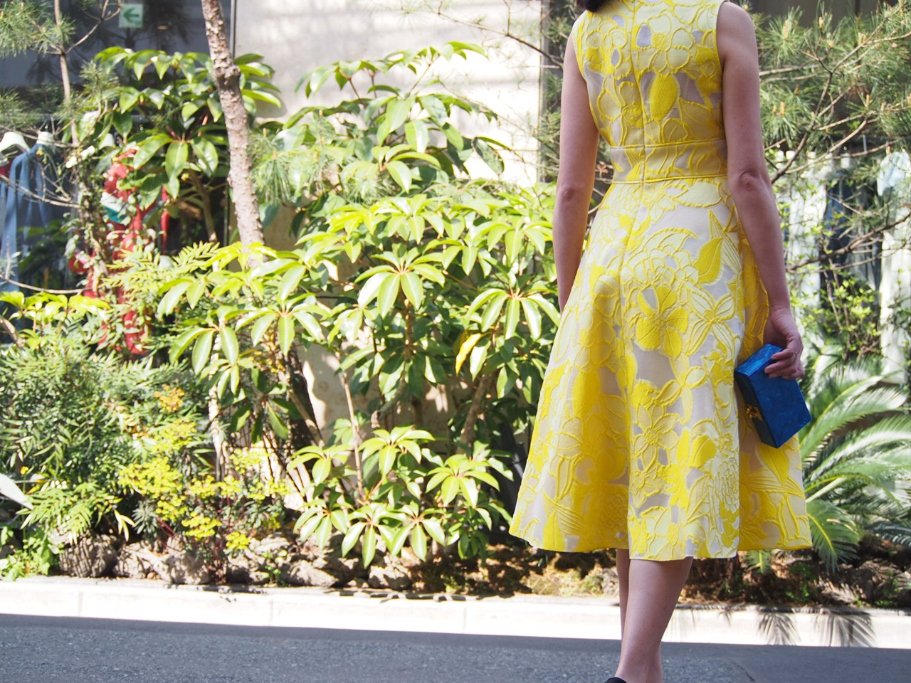 大柄のお花が素敵な黄色のノースリーブドレスには真っ青なブルーのクラッチバッグを合わせると春の結婚式やパーティーにおすすめのおしゃれなレンタルパーティードレス