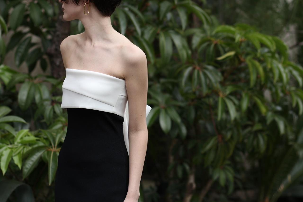 胸元は白でウエストにかけて黒の生地のベアのドレスは身体のラインがでるタイトなシルエット