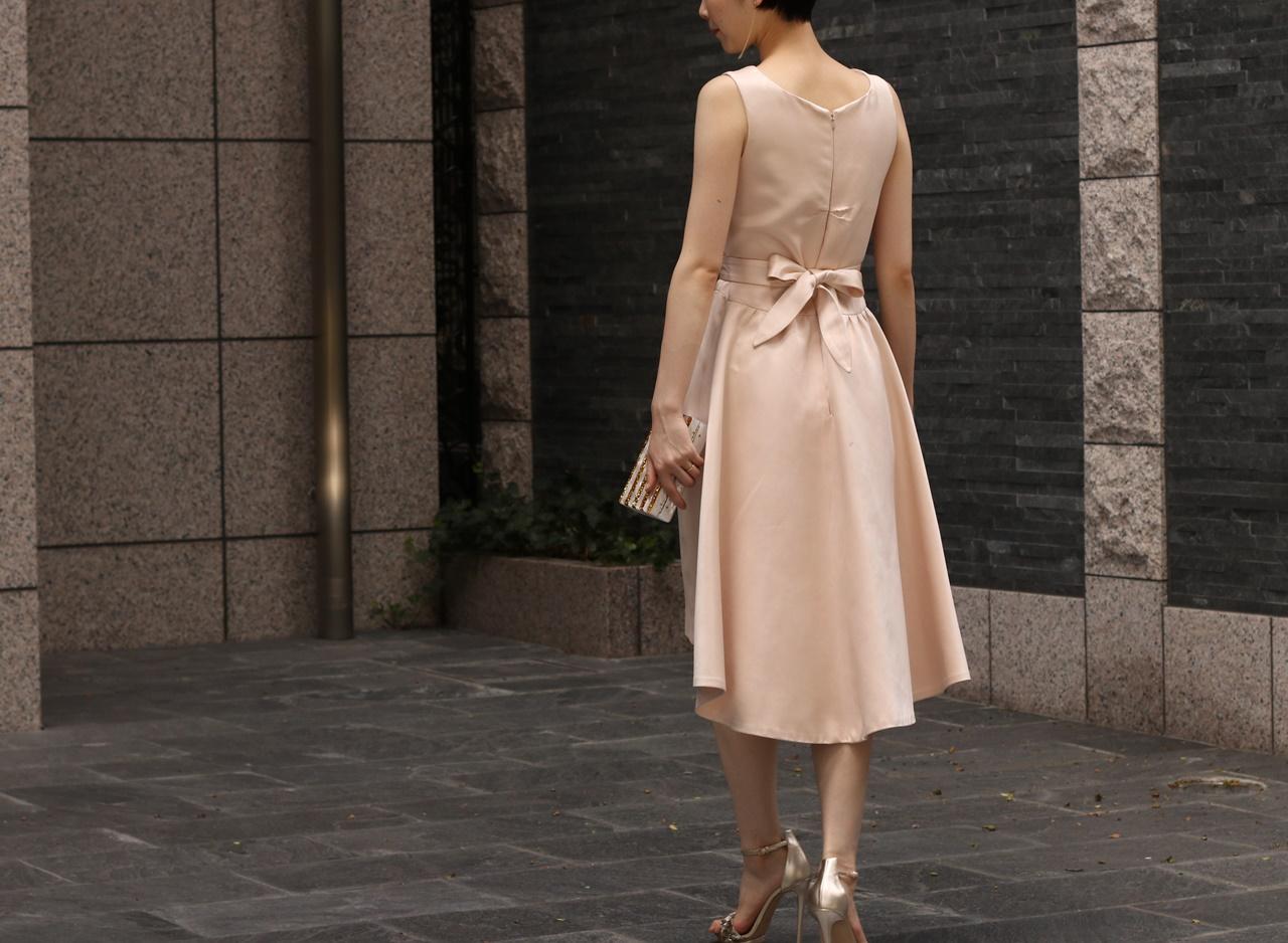 淡いピンクのノースリーブのシルクのドレスはウエストのリボンが可愛い春の結婚式やパーティーにおすすめのおしゃれなレンタルパーティードレス