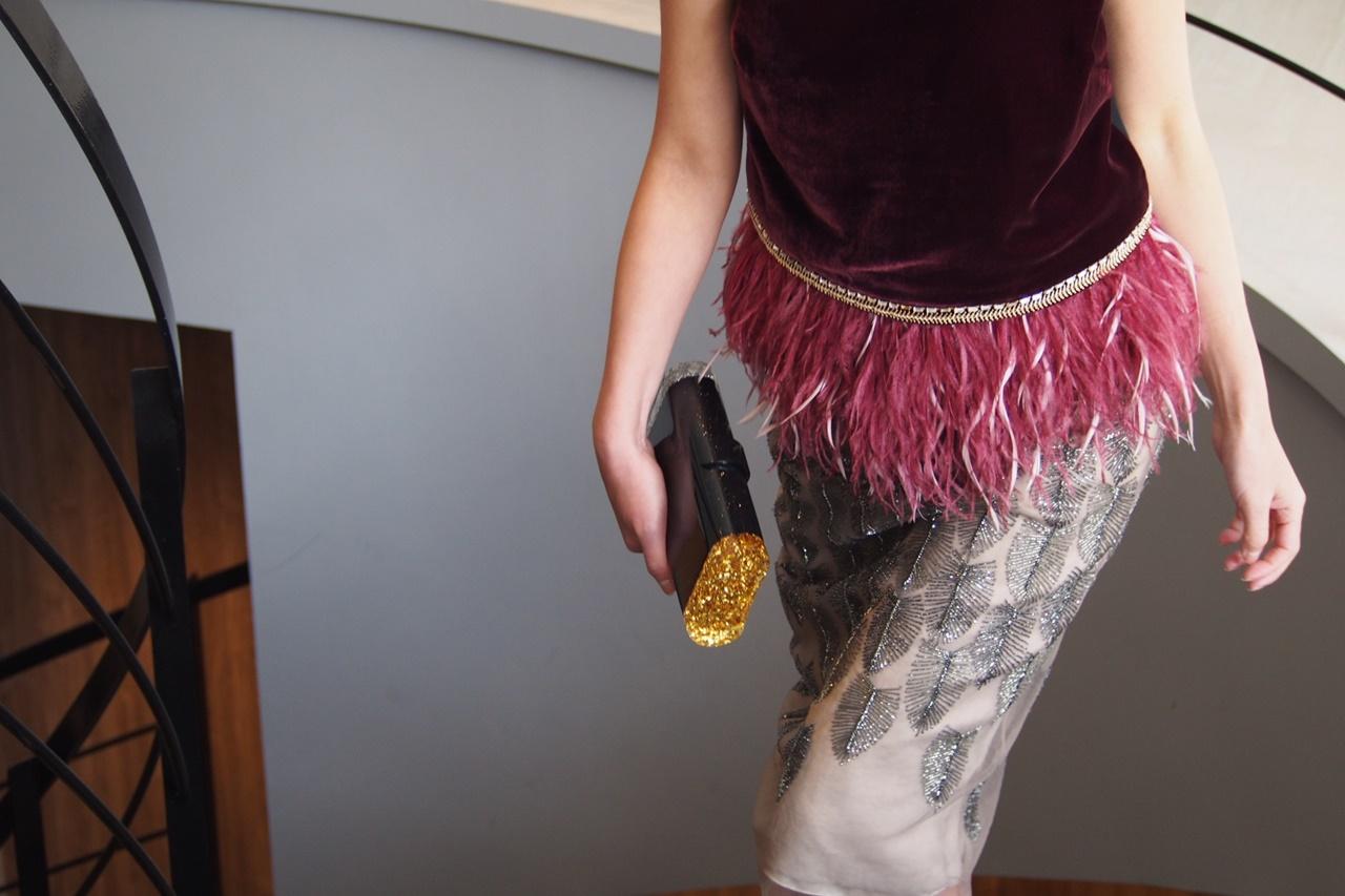 ワインレッドのベルベット生地に裾にリアルファーが付いたトップスとリーフ模様が刺繍されたタイトスカートとのコーディネート