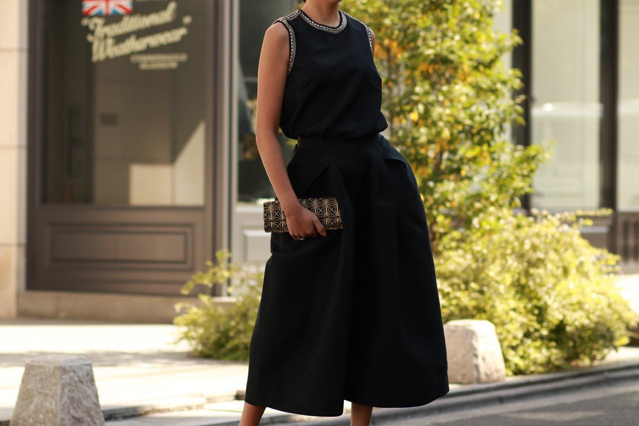衿とアームホールにビジューが一周付いた黒いノースリーブのトップスと足首が見える長さの黒いボリュームのあるタックパンツはクーン・フーイのレンタルパーティードレス