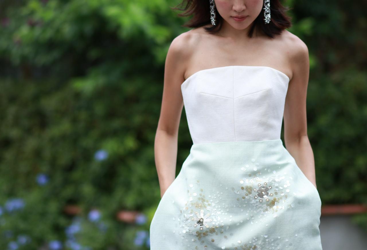 大ぶりなビジューのお花のイヤリングと合わせたデコルテが綺麗に見えるベアトップスのドレスはデルポソのレンタルパーティードレス