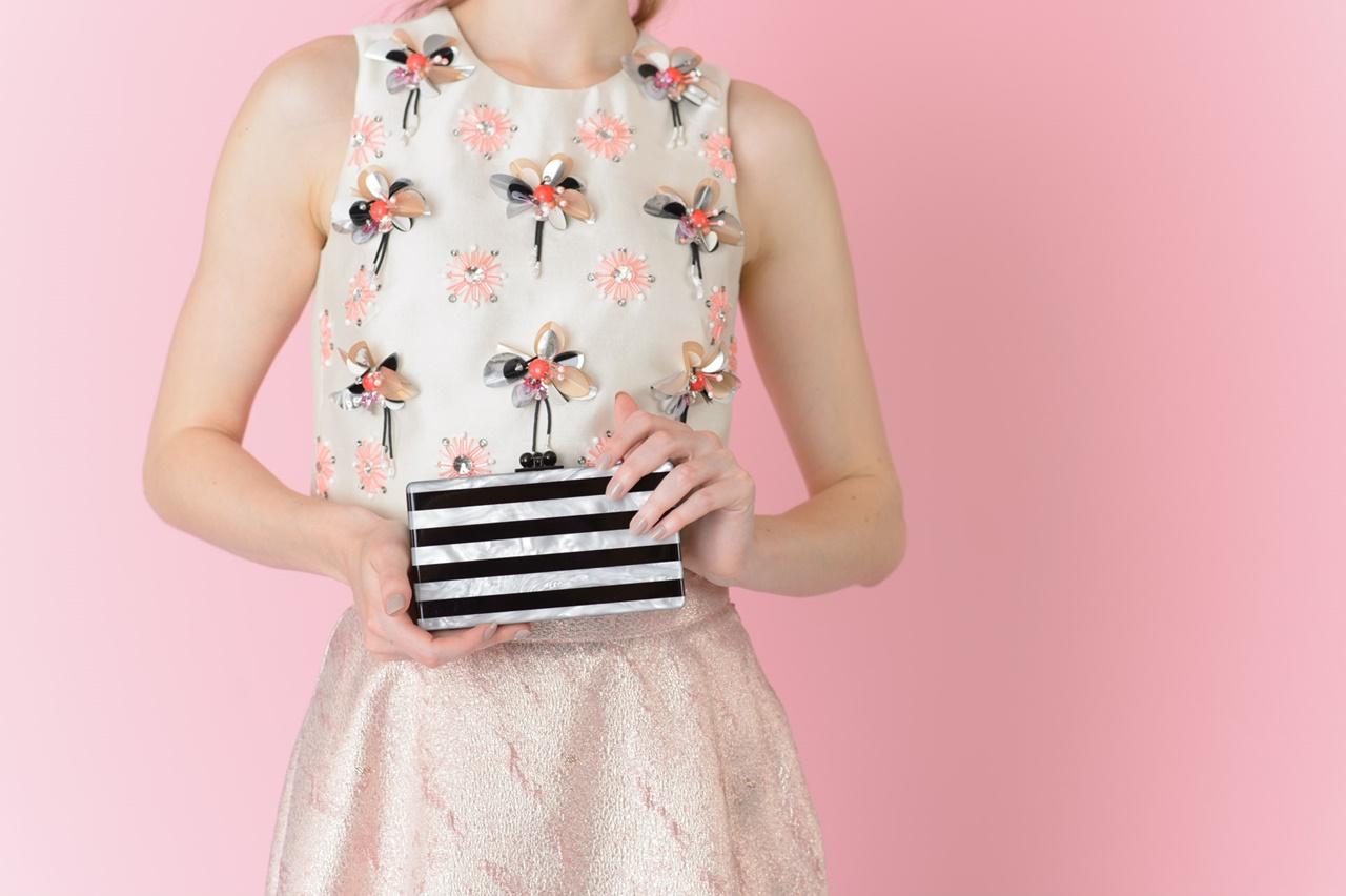 赤やシルバーや黒のビジューが規則的についている白いノースリーブのトップスに光沢のある無図のピンクのスカートを合わせたコーディネート