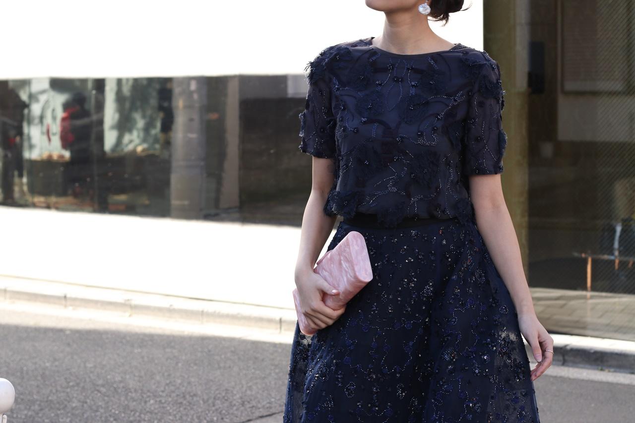 ネイビーの半袖のトップスにはネイビーの刺繍が施されておりネイビーのスカートはスパンコールやビーズを使用して刺繍されたモニークルイリエのレンタルパーティードレス