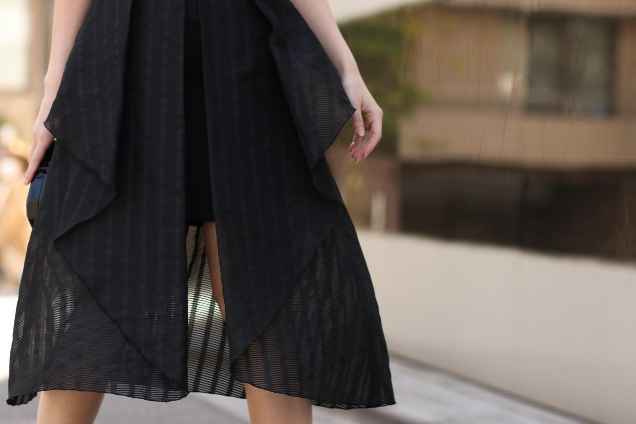 内側が短くなっているので足がうっすら透ける黒いひざ丈のスカートはニコラスのレンタルパーティードレス
