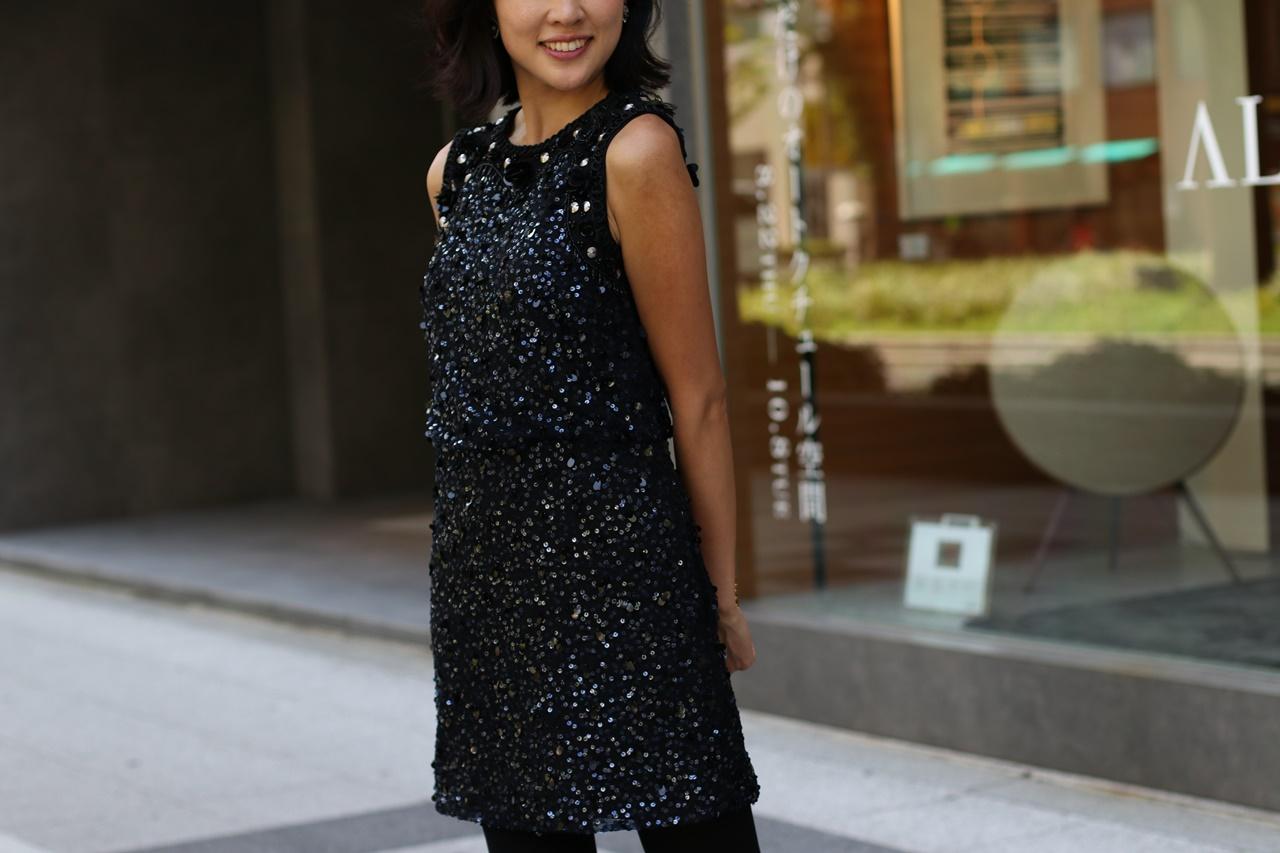 全身にネイビーのスパンコールが施されたひざ丈のノースリーブのワンピースはモニーク・ルイリエ( Monique Lhuillier)のドレス