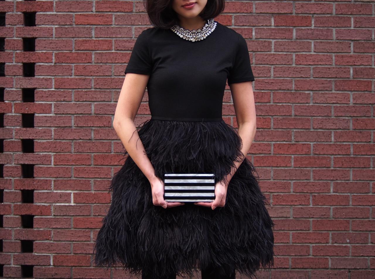 大きなビジューのネックレスを合わせた半袖の黒いドレスはスカ―部分が全てリアルフェザーになっているモーガン・ル・フェイのレンタルパーティードレス