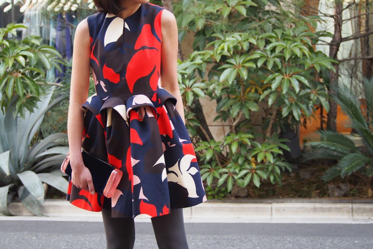 ネイビーベースで赤や白の花模様がプリントされたひざ上丈の立体的なスカートが特徴のドレスはデルポソのレンタルパーティードレス