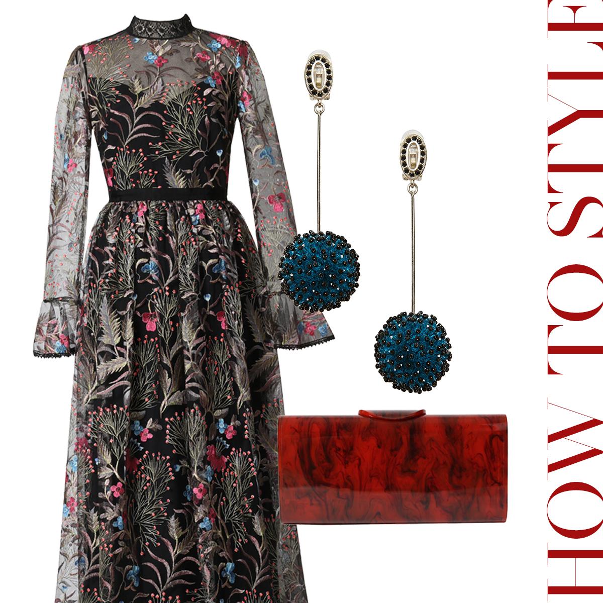 黒のチュールに色鮮やかな刺繍が施された長袖のロングドレスにべっ甲模様のアクリルのクラッチバッグとネイビーのボールが付いた揺れるイヤリングを合わせたおしゃれなコーディネート