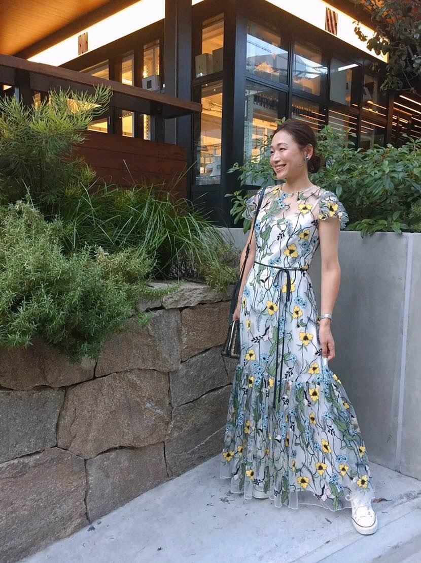 ロングドレスにコンバースのスニーカーを合わせた黒沢祐子さんのパーティースタイル