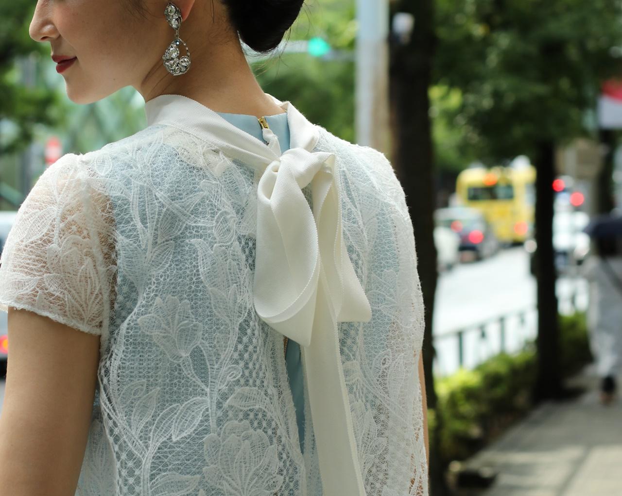 骨格ナチュラルの方におすすめのレンタルドレスはKhon Hooi(クーン・フーイ)の背中にリボンが付いた白いレースのガウンに水色のインナードレスが透けたレンタルドレス